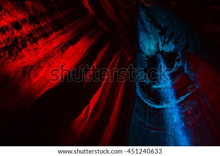 Ruby Falls waterfall illuminated by red and blue light. Waterfall is located in the cavern within Lookout Mountain in Chattanooga, TN. - stock photo