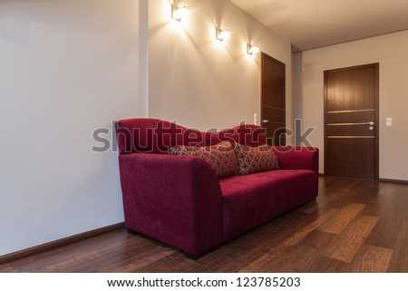 Ruby house - Big sofa on hallway in modern house - stock photo