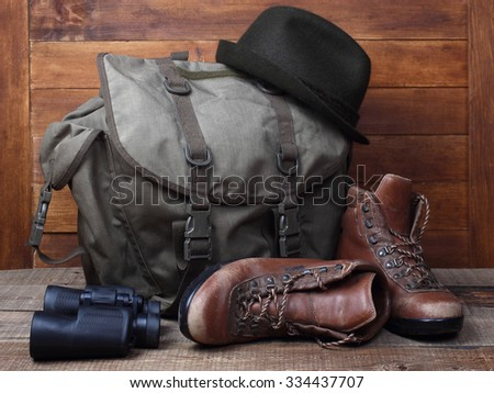 Rucksack with old boots, binocular and hat on wooden background. Traveller concept - stock photo