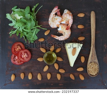 Rucola salad ingredients-rucola leaves, shrimps,almond nuts,tomatoes,sesame seeds,olive oil,cheese- on the old black wooden surface. Top view. Background - stock photo