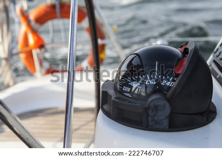 Rudder and compass on a  boat. - stock photo