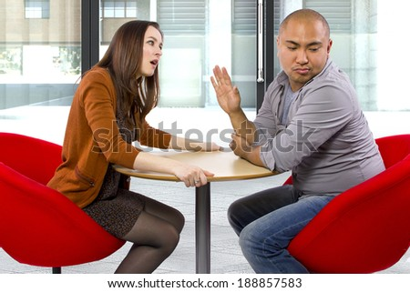 rude interracial couple on a bad date - stock photo