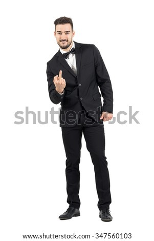 Rude young man in tuxedo with bow tie showing middle finger gesture at camera.  Full body length portrait isolated over white studio background.  - stock photo