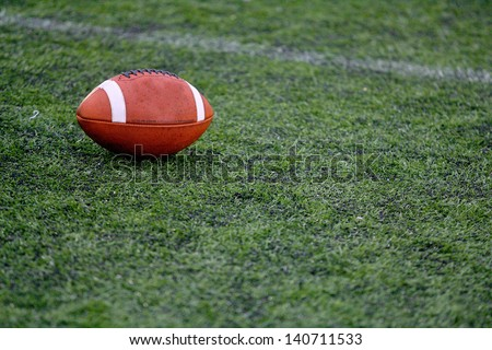 Rugby ball at green grass american foodball - stock photo