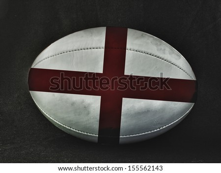 Rugby ball with England flag colors, over black background - stock photo