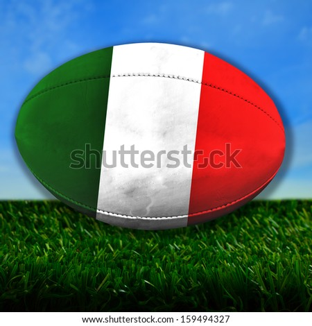 Rugby ball with Italy flag over grass - stock photo