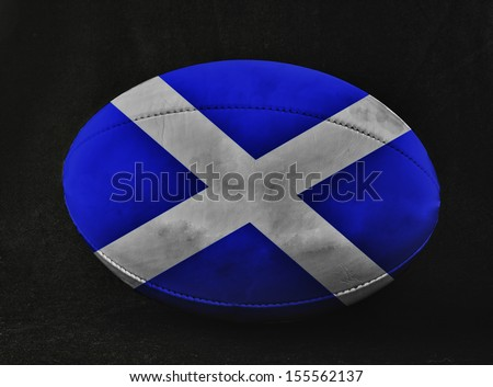 Rugby ball with Scotland flag colors, over black background - stock photo