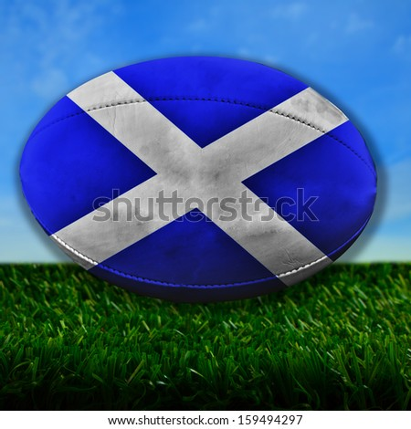 Rugby ball with Scotland flag over grass - stock photo