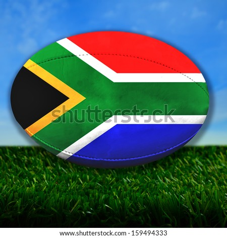 Rugby ball with South Africa flag over grass - stock photo