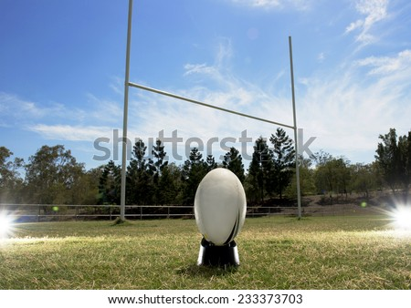 Rugby football in front of the goal posts, with lighting effects either side - stock photo