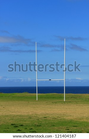 Rugby goalposts. Sports field with white uprights contrasting with the blue sea and blue sky background.  Sports field with a blue sky and blue sea background - stock photo