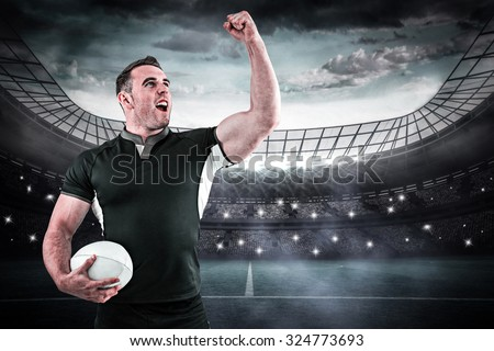 Rugby player cheering with the ball against large football stadium under blue sky - stock photo