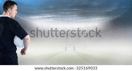 Rugby player gesturing with hands against rugby pitch - stock photo