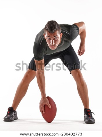 Rugby player holding a ball on white background.Strong player portrait. - stock photo