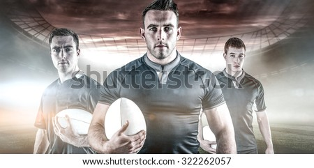 Rugby player holding a rugby ball against rugby pitch - stock photo