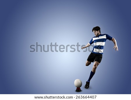 Rugby player in a blue uniform kicking a ball on a blue background. - stock photo