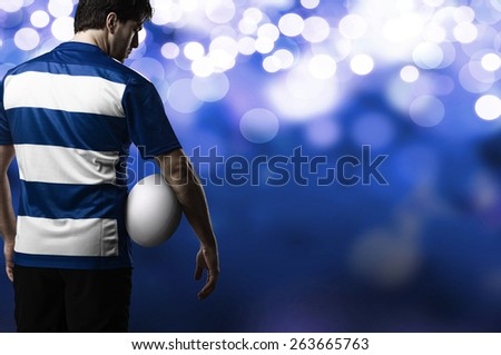 Rugby player in a blue uniform on a blue lights background. - stock photo