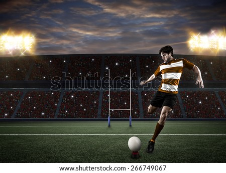 Rugby player in a orange uniform kicking a ball on a stadium. - stock photo