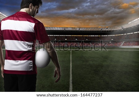 Rugby player in a red uniform in a stadium. - stock photo