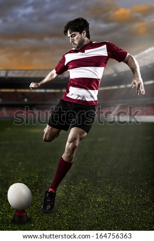 Rugby player in a red uniform kicking a ball on the Stadium - stock photo