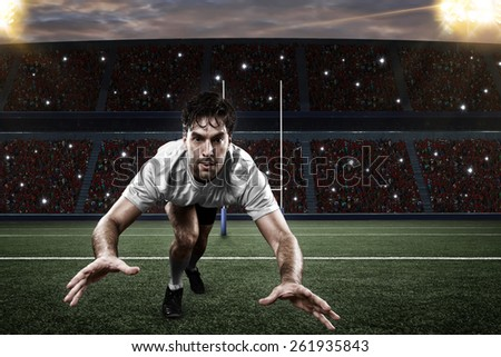 Rugby player in a white uniform giving a tackle on a stadium. - stock photo