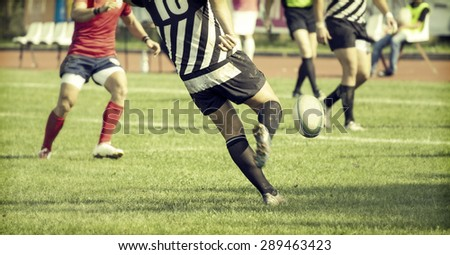 Rugby player kicking hard the oval ball - sports concept, retro style photo - stock photo