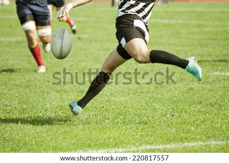 Rugby player legs kicking the oval ball - stock photo