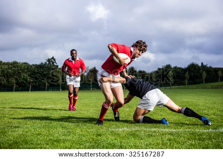Rugby players tackling during game at the park - stock photo