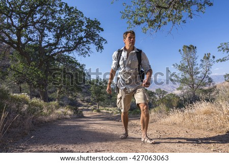 Rugged Caucasian outdoorsman hikes with backpach and sandals on dirt road in California mountains - stock photo