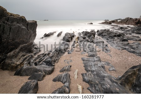 Rugged long exposure landscape seascape of rocky coastline - stock photo