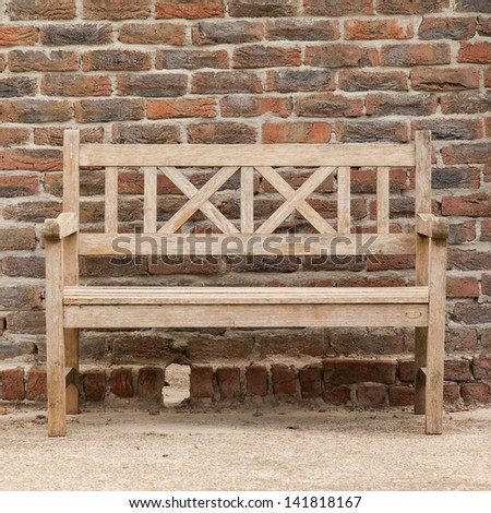 Rugged, primitive wooden sidewalk bench beside multi-colored very old brick wall background - stock photo