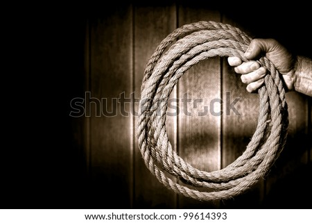 Rugged rancher cowboy hand firmly holding a ranching rope in a loop in an old rustic barn with dramatic light in nostalgic sepia - stock photo