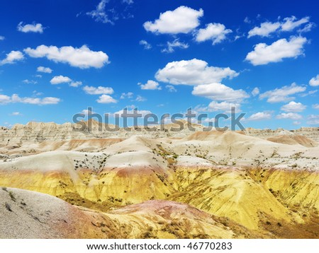 Rugged terrain in Badlands National Park, South Dakota, beneath blue sky and clouds. Horizontal shot. - stock photo