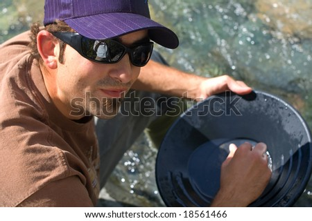 Rugged young man gold panning at a creek. - stock photo