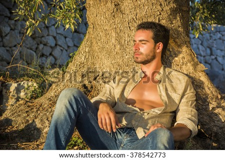 Ruggedly Handsome Man Seated at Base of Tree with Shirt Unbuttoned and Eyes Closed Relaxing in Warm Sunlight - stock photo