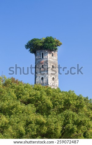 Ruin of an ancient tower surrounded by lush green trees, Jiangxin Island, Wenzhou, Zhejiang Province, China - stock photo