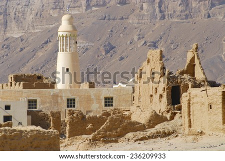 Ruin of an old mud brick fortress and a village mosque near the city of Seiyun, Yemen. - stock photo