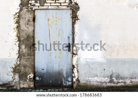 Ruined brick wall with closed steel door - stock photo