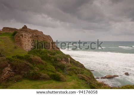 Ruined crusader castle on a stormy beach - stock photo