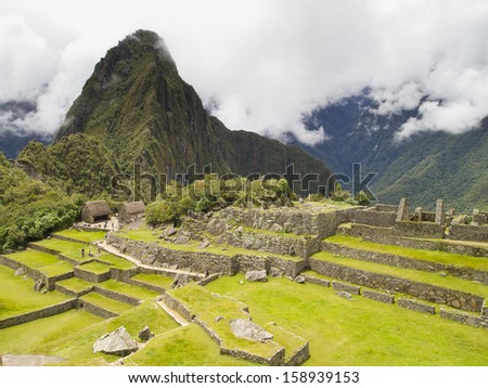 Ruins Buildings in Machu Picchu - Mysterious city and archaeological site of pre-Columbian civilization of the Incas on the Andes cordillera mountains archaeology near Cusco, Peru. - stock photo