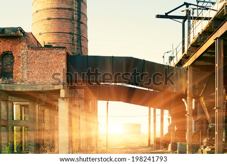 Ruins of a very heavily polluted industrial factory backlit at sunset - stock photo
