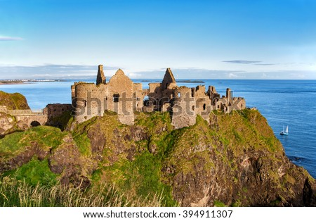 Ruins of Dunluce castle in County Antrim, Northern Ireland, UK, with the far view of  Portrush resort on the left - stock photo