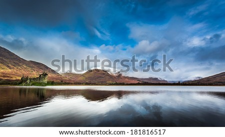 Ruins of old castle in Scotland over the lake - stock photo