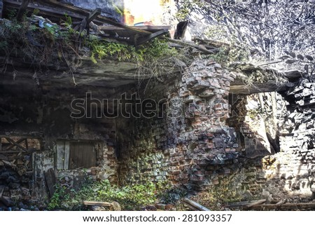Ruins of shabby building covered by vegetation. This building is very old and not inhabited for a long time. Brick walls are blasted. Some color effects give uniqueness to the picture. - stock photo