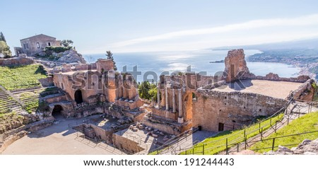 Ruins of the ancient greek theater of Taormina, Sicily with the morning sunshine reflecting from the Giardini-Naxos bay of the Ionian see. - stock photo