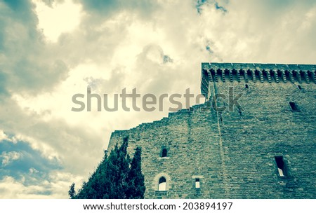 Ruins of the medieval castle and cypress tree before a storm. (Chateauneuf du Pape, Provence, France) Nature and architecture background. Aged photo. - stock photo