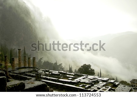 Ruins of the Temple of Apollo at Delphi, Greece in a rainstorm with clouds rolling down the valley - stock photo