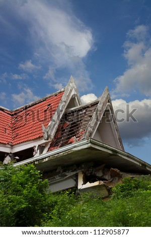 Ruins of the thai house has red roof broken down which is located clouds and sky. - stock photo