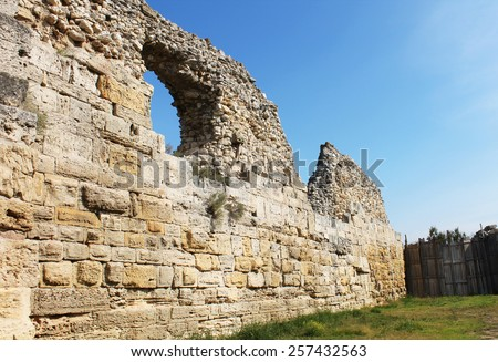 Ruins wall of an old town against the blue sky - stock photo