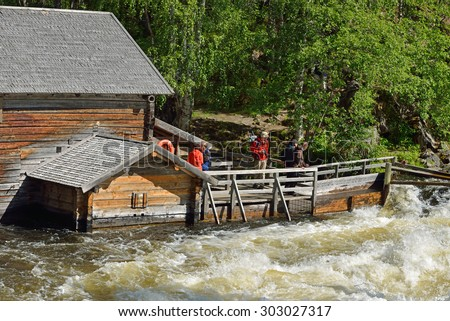 RUKA, FINLAND - JULY 7,2015:Old watermill at Myllykoski used to grind barley and rye until late 1940s. Today it serves as rest hut for hikers with open fireplace and scenic views of Myllykoski Rapids - stock photo